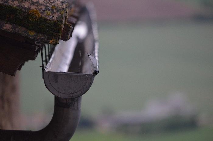 Canalones enganchados bajo las tejas